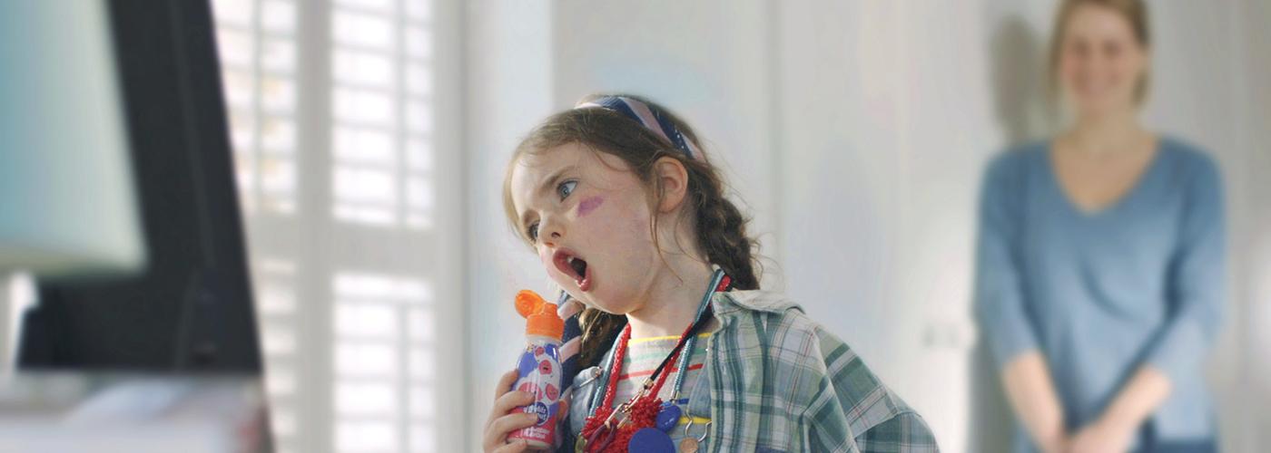 Une jeune fille qui chante dans un yaourt smoothie de Petits Filous tandis que sa mère la regarde et sourit